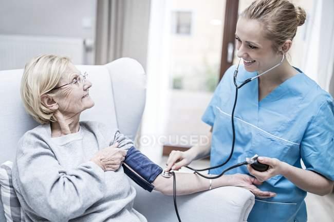 Krankenschwester nimmt Blutdruck von Seniorin. — Stockfoto