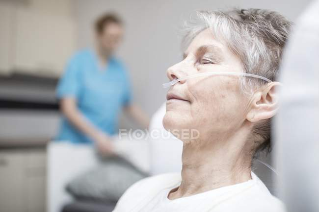 Senior woman sleeping with nasal cannula and nurse in background, close-up. — Stock Photo