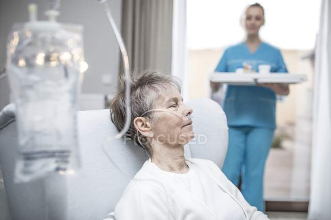 Senior woman with nasal cannula and IV bag and nurse holding tray in background, close-up. — Stock Photo