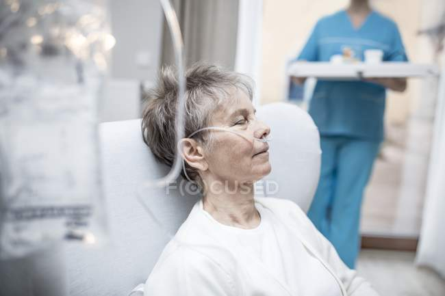Senior woman with nasal cannula and IV bag and nurse holding tray in background. — Stock Photo