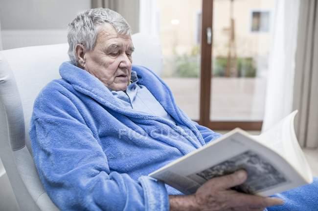Senior man in blue bathrobe reading magazine in care home. — Stock Photo