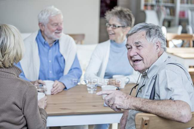 Friends talking and smiling at table with drinks in retirement home. — Stock Photo