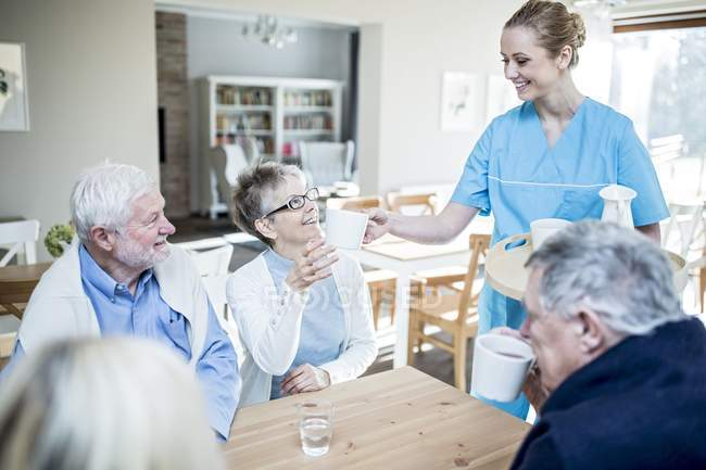 Female caregiver serving tea to senior adults in care home. — Stock Photo