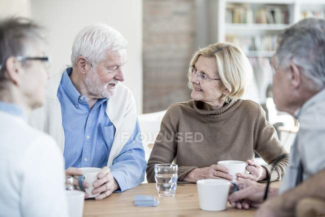 Senior friends talking at table with cups and glass of water in retirement home. — Stock Photo