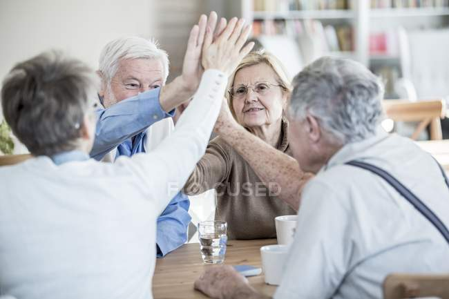 Friends giving high fives while sitting at table in retirement home. — Stock Photo