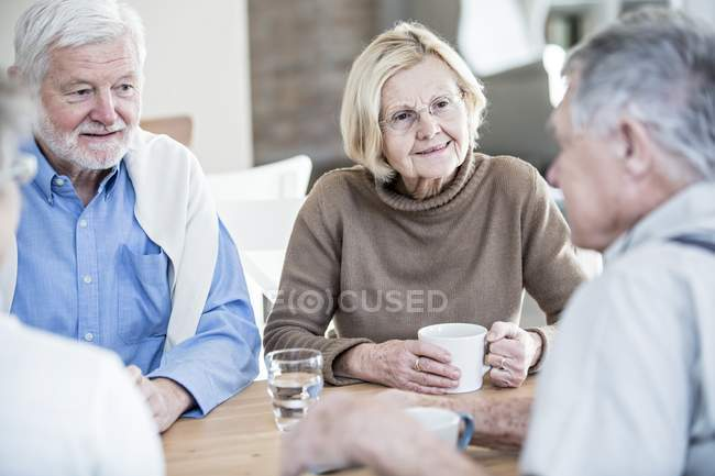 Senior friends talking in retirement home at table with drinks. — Stock Photo
