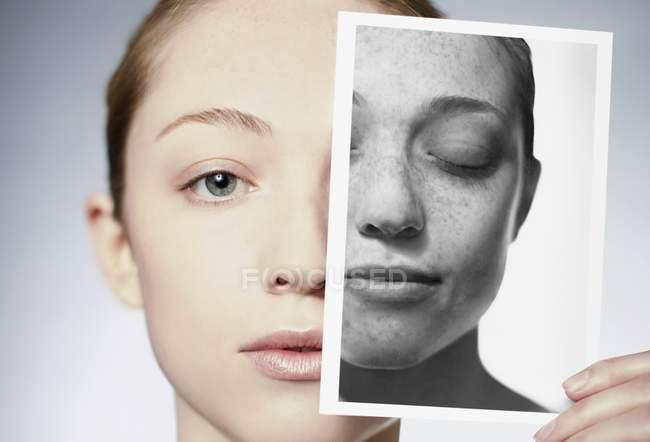 Женщина, держащая фотографию перед лицом, показывает повреждение кожи на солнце . — стоковое фото