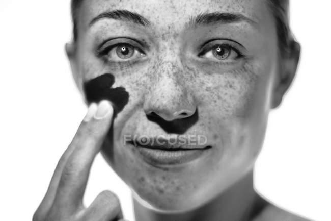 Молодая женщина с веснушками наносит солнцезащитный крем на щеку . — стоковое фото