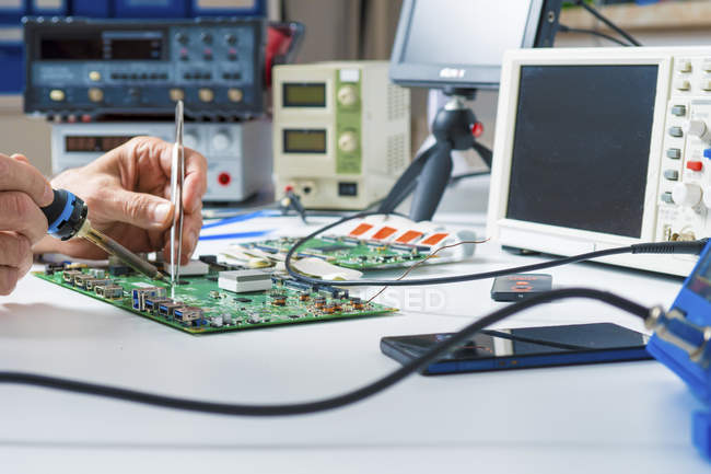 Close-up of male hands repairing circuit board. — Stock Photo