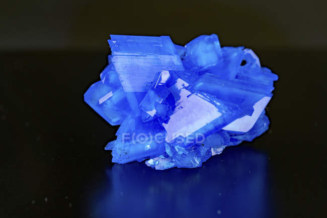 Blue mineral gemstone on mirror surface. — Stock Photo