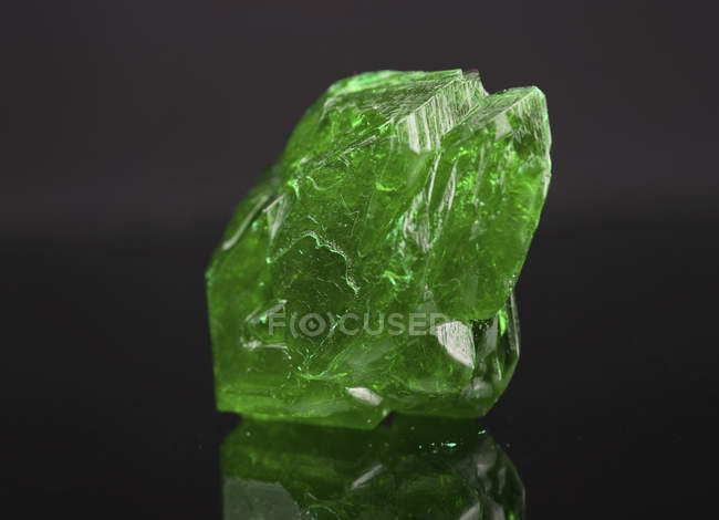 Green mineral gemstone on mirror surface. — Stock Photo