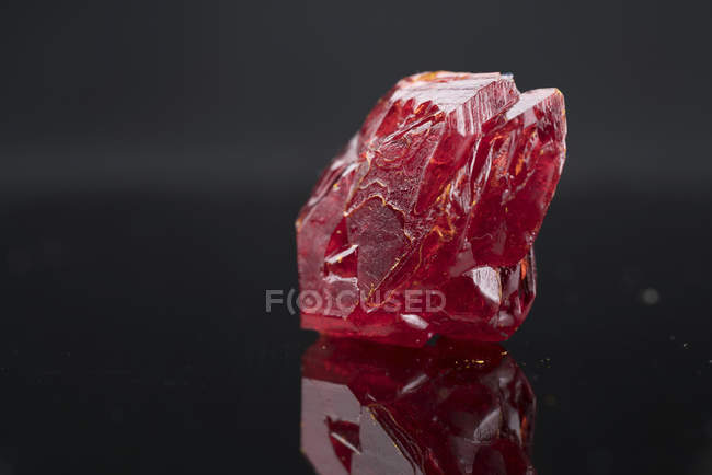 Red mineral gemstone on mirror surface. — Stock Photo