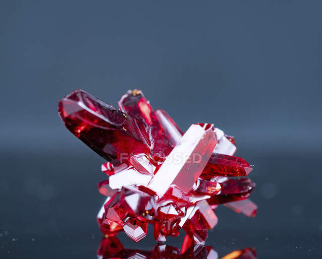 Red mineral crystals on gray background. — Stock Photo