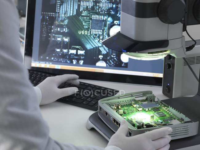 Cropped view of engineer using stereo microscope for inspecting printed circuit board. — Stock Photo