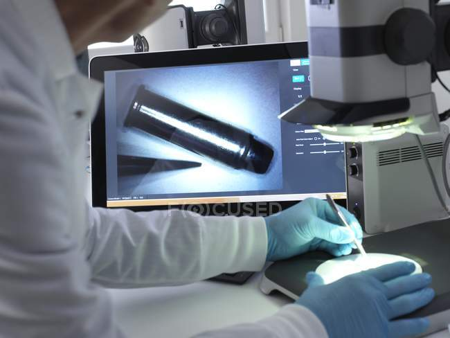 Forensic scientist using 3d stereo microscope for examining markings on bullet. — Stock Photo