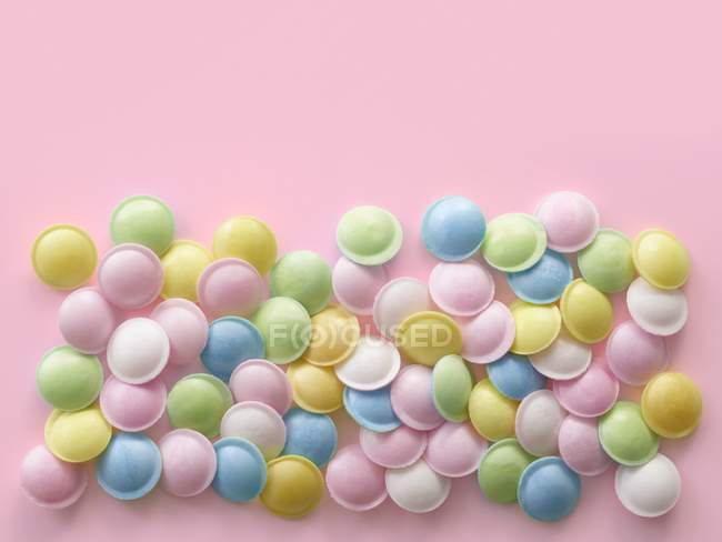 Pastel colored sweets against pink background. — Stock Photo