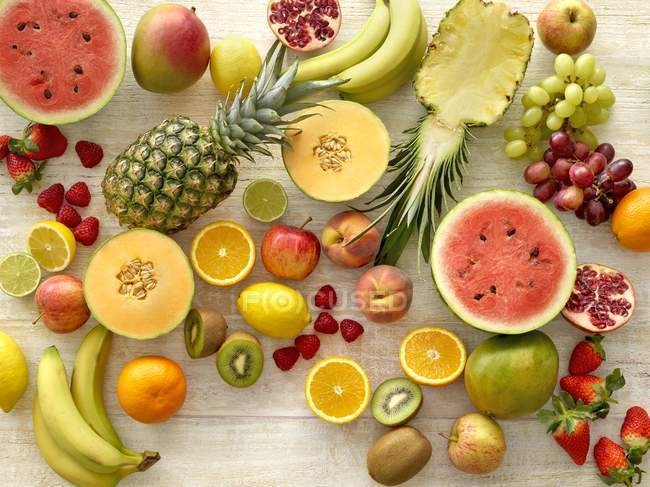 Variety of fresh fruits on wooden background. — Stock Photo