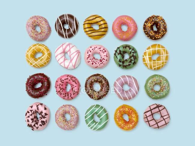 Vista superior de rosquillas de colores en el fondo, toma de estudio . - foto de stock