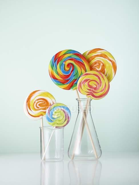 Artículos de vidrio de laboratorio con piruletas de colores . - foto de stock