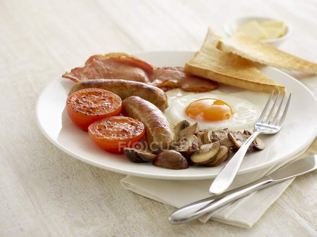 Full English breakfast served on plate on table. — Stock Photo