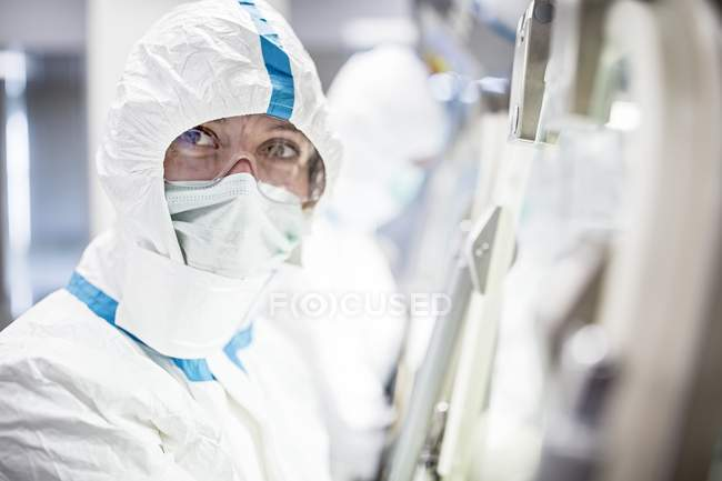 Lab technician in protective suit, face mask and safety goggles in sterile laboratory. — Stock Photo
