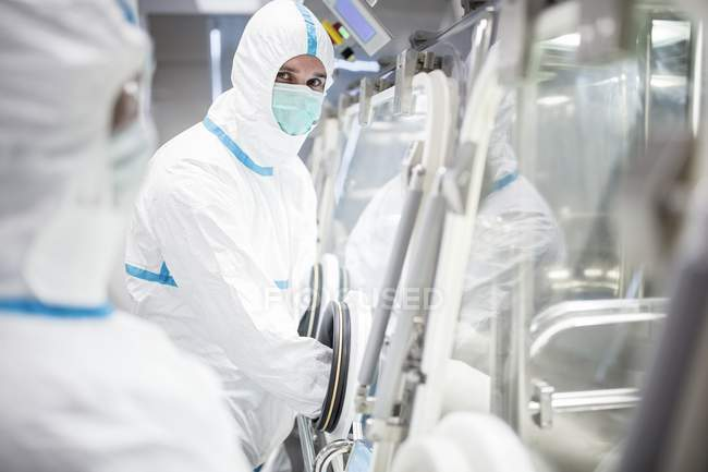 Technicians working with glovebox in sealed and sterile biomedical laboratory. — Stock Photo