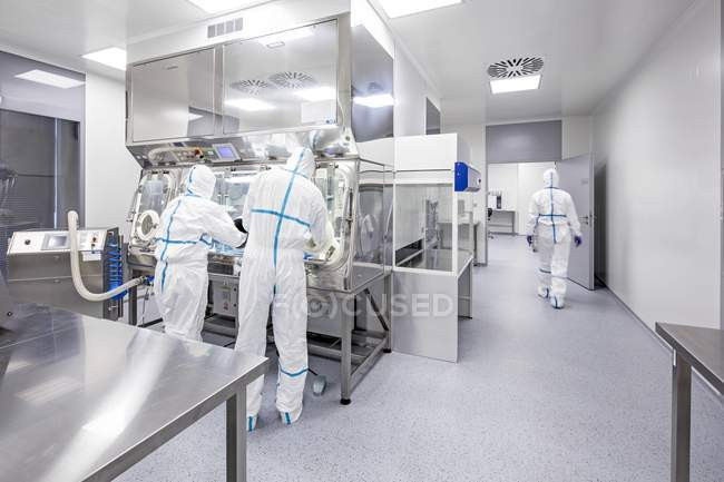 Técnicos que trabalham no laboratório biomédico lacrado e estéril. — Fotografia de Stock