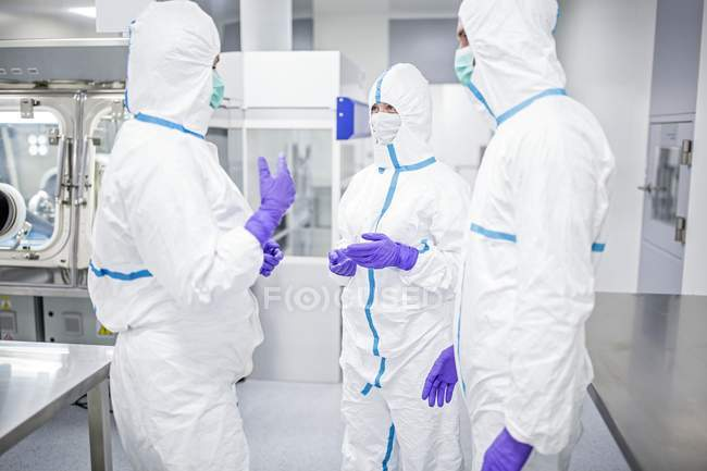 Lab technicians in protective suits and masks discussing in sterile laboratory environment. — Stock Photo