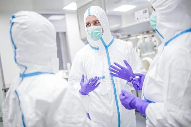 Técnicos de laboratório em trajes de proteção e máscaras discutindo em ambiente de laboratório estéril . — Fotografia de Stock