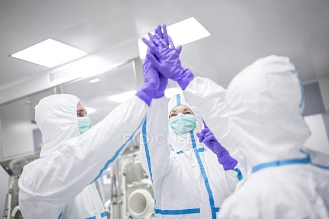 Técnicos de laboratório altamente cinco em ambiente de laboratório estéril . — Fotografia de Stock