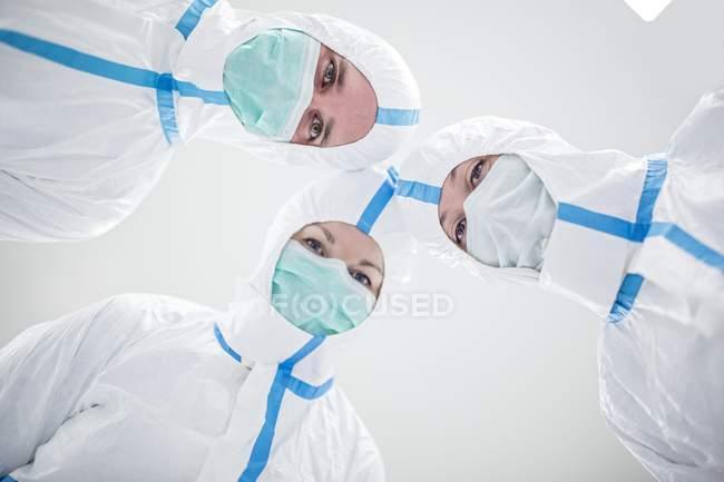 Técnicos de laboratório em trajes de proteção e máscaras olhando na câmera em laboratório estéril. — Fotografia de Stock