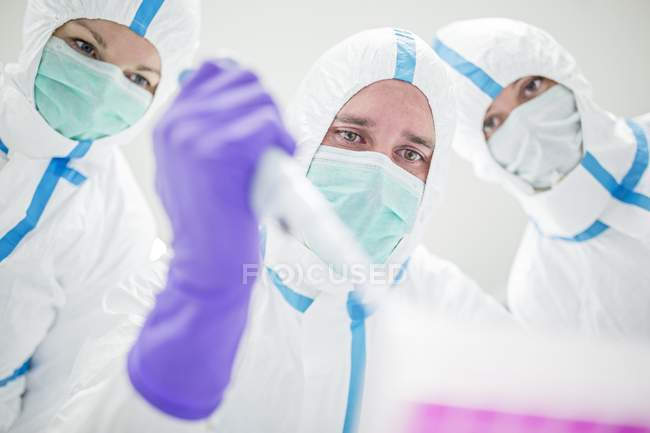 Lab technicians in protective suits and masks pipetting in sterile laboratory. — Stock Photo