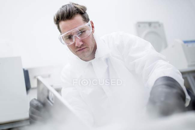 Male technician in safety goggles opening steaming cryostorage. — Stock Photo