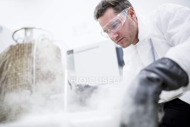 Technicien masculin en lunettes de sécurité ouvrant cryostockage vapeur . — Photo de stock