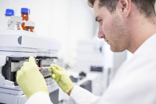 Technician placing glass column with calibration solution to mass spectrometer. — Stock Photo