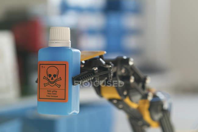 Bras robotisé tenant bouteille de produit chimique dangereux. — Photo de stock
