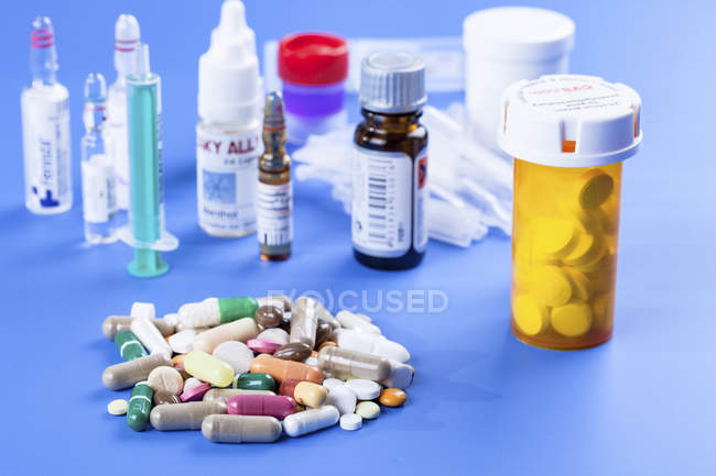 Assorted medicines and supplements on blue background. — Stock Photo