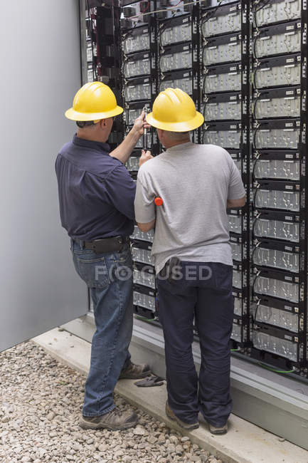 Engineers connecting energy storage batteries for backup power to electric power plant. — Stock Photo