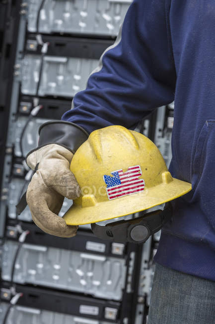 Close-up of engineer in rubber protective glove carrying hard hat with US flag. — Stock Photo