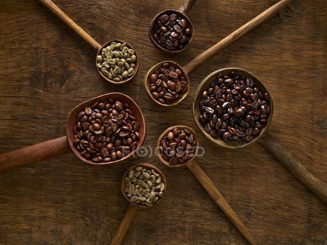 Wooden spoons with coffee beans on rustic background. — Stock Photo