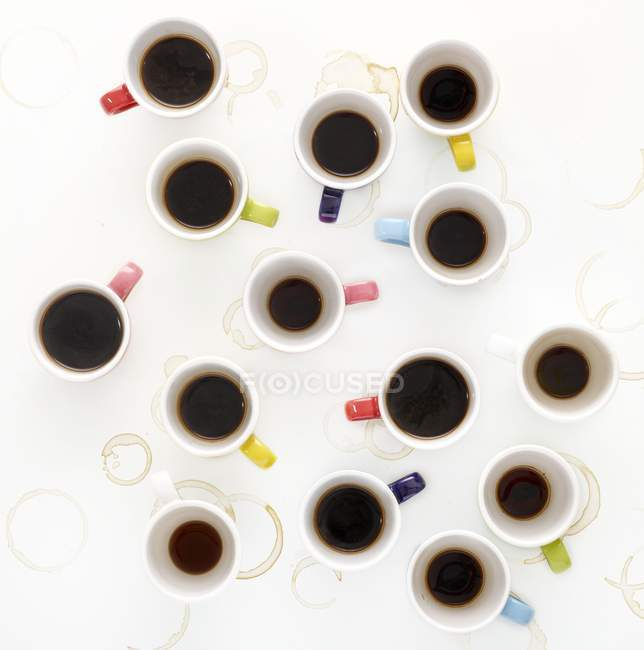 Colorful cups of coffee on table, high angle view. — Stock Photo