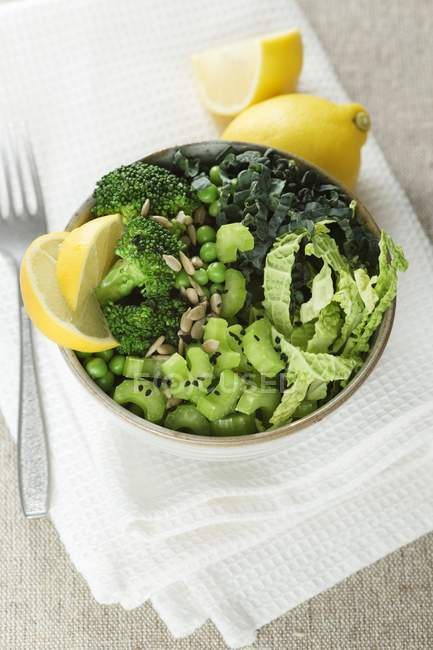 Various sliced green vegetables in salad bowl with lemon. — Stock Photo