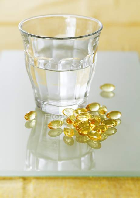 Evening primrose oil capsules in pile next to transparent glass of water. — Stock Photo