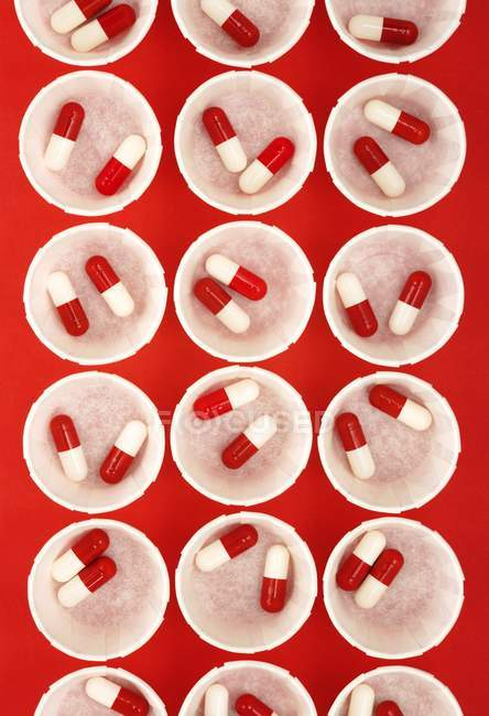 Top view of paper medicine pots with red and white drug capsules. — Stock Photo