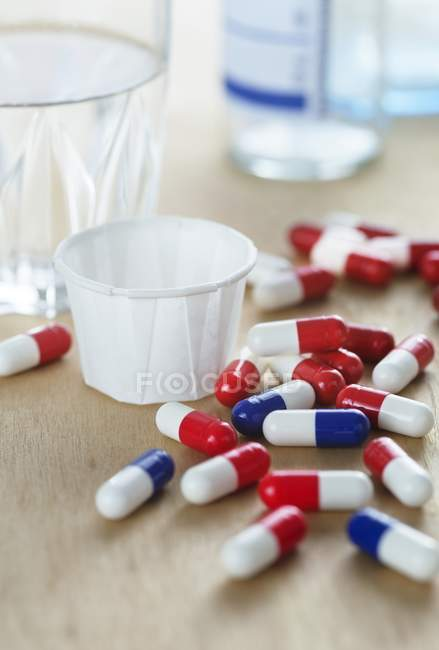 Red and white and blue and white drug capsules by glass of water. — Stock Photo