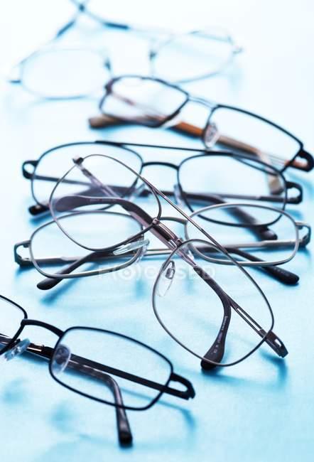 Gros plan de différentes paires de lunettes sur la surface bleue . — Photo de stock