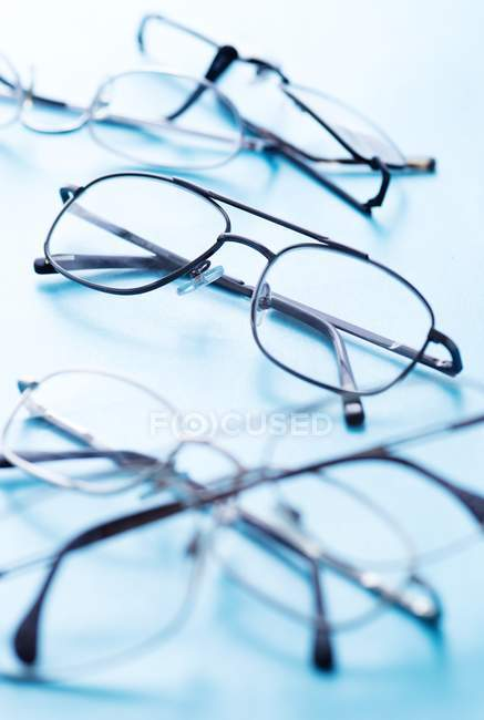 Close-up of various pairs of eyeglasses on blue surface. — Stock Photo