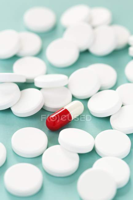 Round white pills surrounding oval red and white capsule. — Stock Photo