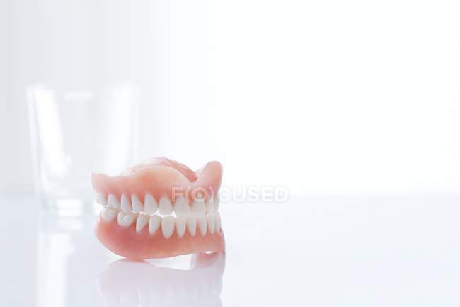 Dentures on table against white background. — Stock Photo
