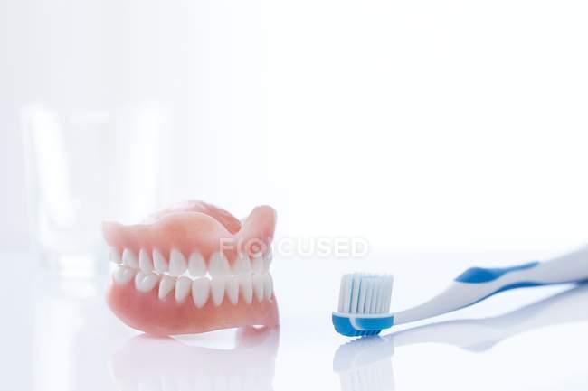 Dentiere e spazzolino da denti su sfondo bianco, ripresa in studio . — Foto stock